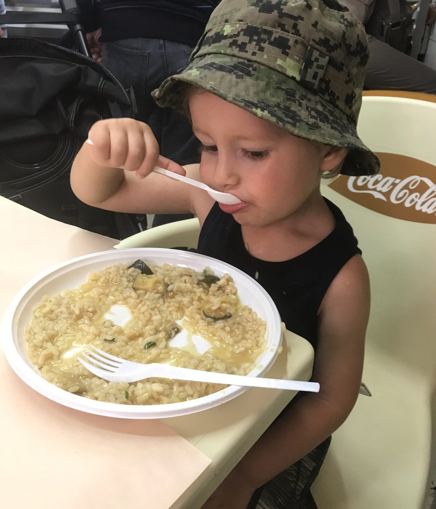 Boy eating risotto in Catania