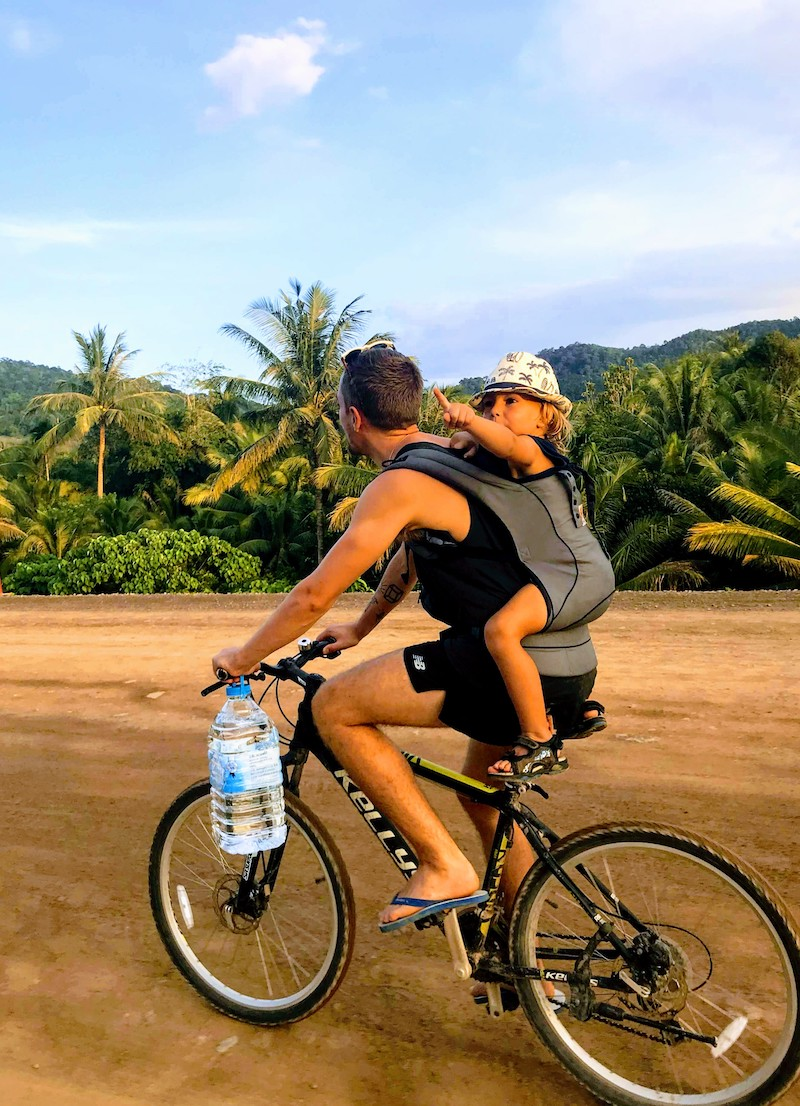 Biking on Koh Lanta, with a kid on the bag