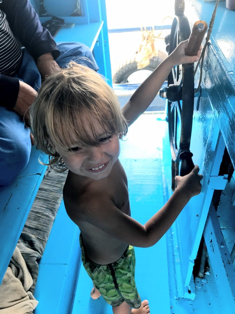 Kid holding the steering wheel on diving ship at Koh Tao