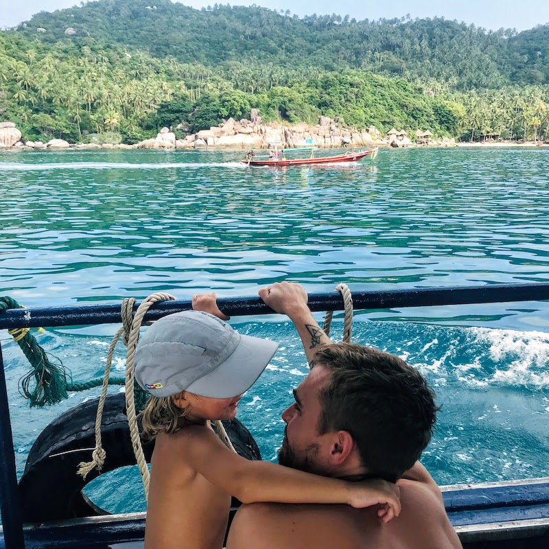 Dad and son on the boat, longtail boat and Koh Tao in the background